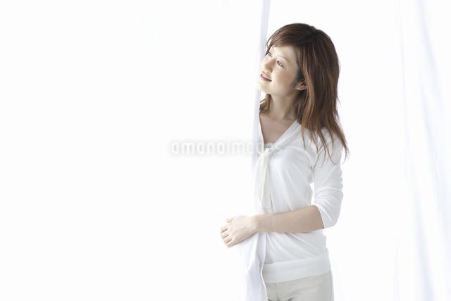 カーテン越しに微笑む女性の写真素材 [FYI04128959]