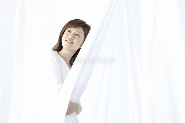 カーテン越しに微笑む女性の写真素材 [FYI04128967]
