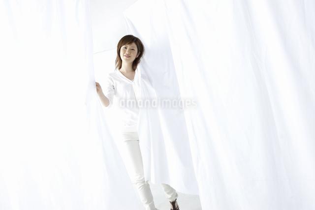 カーテン越しに微笑む女性の写真素材 [FYI04128968]