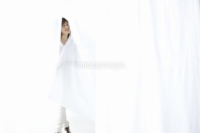 カーテン越しに微笑む女性の写真素材 [FYI04128970]