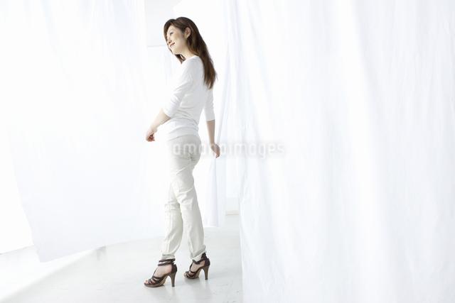 カーテン越しに微笑む女性の写真素材 [FYI04128976]
