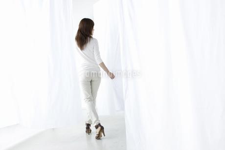 カーテンの中を歩く女性の写真素材 [FYI04128977]