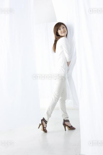 カーテン越しに微笑む女性の写真素材 [FYI04128978]