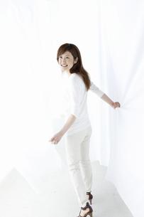 カーテンの中を歩く女性の写真素材 [FYI04128980]