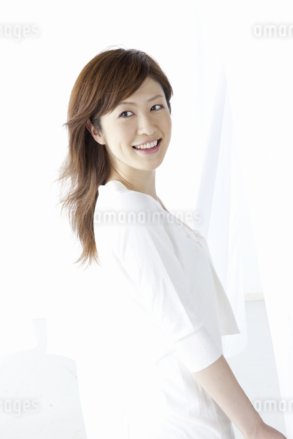 カーテン越しに微笑む女性の写真素材 [FYI04128984]