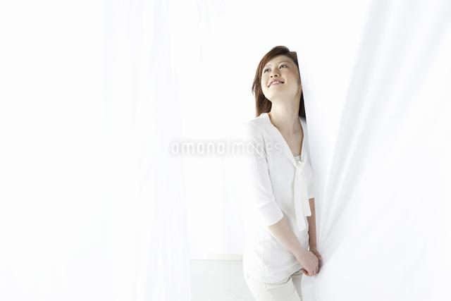 カーテン越しに微笑む女性の写真素材 [FYI04128985]