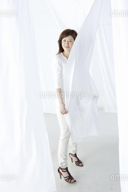 カーテン越しに微笑む女性の写真素材 [FYI04128993]