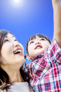 青空をバックに笑顔で見上げる親子。愛情、幸せ親子のイメージの写真素材 [FYI04132791]