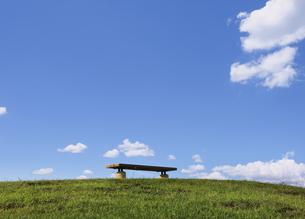 ちぎれ雲と公園の丘のベンチの写真素材 [FYI04134237]