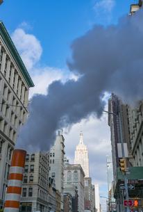 冬の五番街に建ち並ぶ高層ビル群の間に漂う蒸気とエンパイヤーステートビル。の写真素材 [FYI04137168]