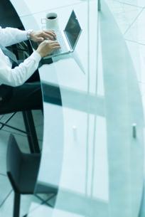 カウンターで仕事をするビジネスマンの手元の写真素材 [FYI04145192]