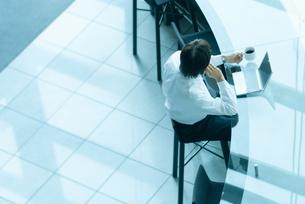 カウンターで仕事をするビジネスマンの写真素材 [FYI04145193]