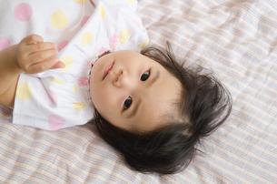 ベッドに寝転がっている女の子の写真素材 [FYI04153686]