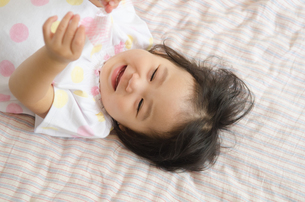 ベッドの上で笑っている女の子の写真素材 [FYI04153734]