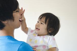 お父さんの顔を触っている女の子の写真素材 [FYI04153845]