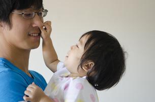 お父さんの顔を触っている女の子の写真素材 [FYI04153899]