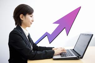 ノートパソコンで株価をチェックする女性の写真素材 [FYI04154313]