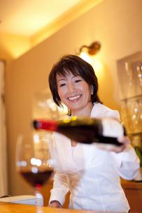 グラスにワインを注ぐソムリエの女性の写真素材 [FYI04154472]