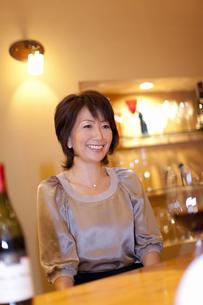 お客さんと笑顔で会話するソムリエの女性の写真素材 [FYI04154523]