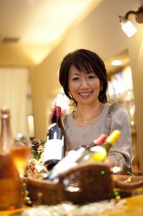 ワインボトルを片手に笑顔の女性の写真素材 [FYI04154598]