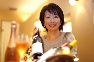 ワインボトルを片手に笑顔の女性の写真素材 [FYI04154599]
