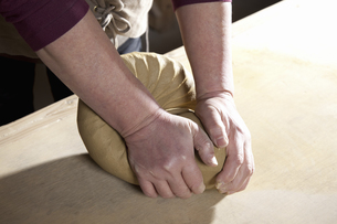 土を練る陶芸家の写真素材 [FYI04171062]