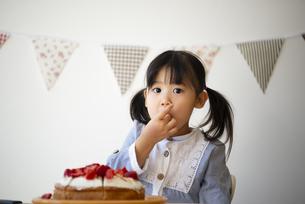 ケーキのいちごを食べている女の子の写真素材 [FYI04171266]