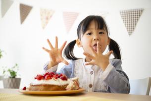 ケーキの前で指をなめている女の子の写真素材 [FYI04172527]