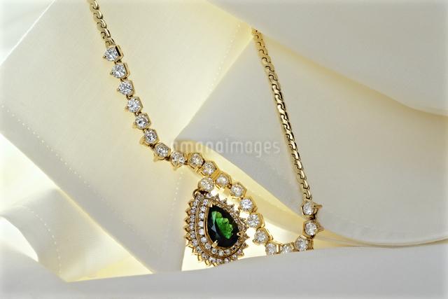シルクのブラウスに絡むダイヤで飾られたエメラルドのペンダントの写真素材 [FYI04172898]
