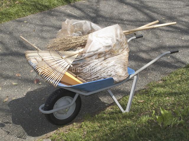 掃き掃除した後に一輪車でゴミを運ぶの写真素材 [FYI04176927]