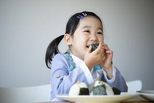 おにぎりを食べている女の子の写真素材 [FYI04179285]