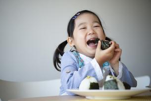 おにりぎを食べながら笑っている女の子の写真素材 [FYI04179781]