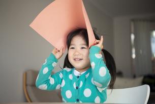 画用紙を頭の上に乗せている女の子の写真素材 [FYI04180727]