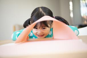 画用紙の隙間からのぞいている女の子の写真素材 [FYI04181016]