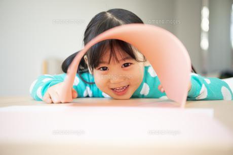 画用紙の隙間からのぞいている女の子の写真素材 [FYI04181308]