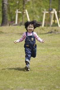 芝生の上を走る女の子の写真素材 [FYI04183324]