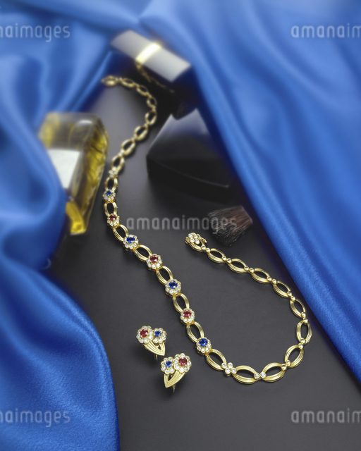 化粧品とアクセサリーが青いシルクの隙間にの写真素材 [FYI04184410]