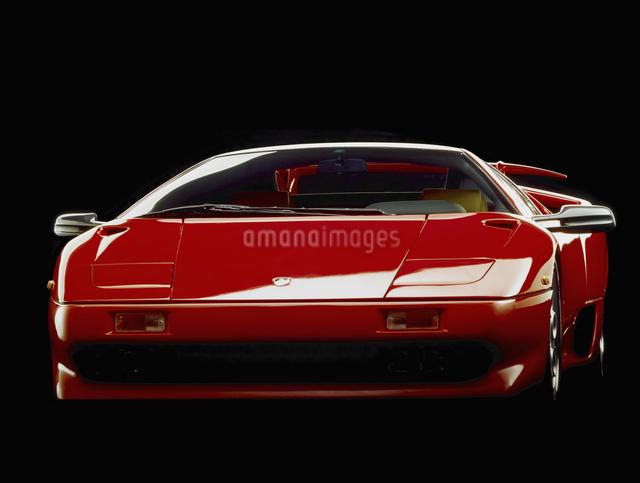 黒バックで撮影された赤いスーパーカーのフロントビューの写真素材 [FYI04184424]
