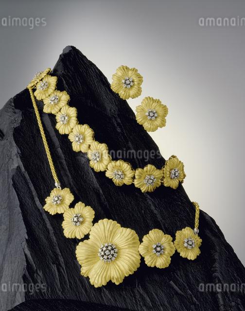 玄昌石にディスプレーされた花がモチーフのアクセサリーの写真素材 [FYI04184450]