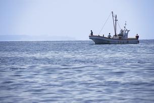岬の沖で釣り糸を垂らす釣り船の写真素材 [FYI04184506]