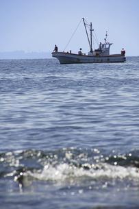 岬の沖で釣り糸を垂らす釣り船と浅瀬の波の写真素材 [FYI04184508]