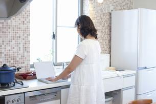 キッチンでノートパソコンを見るお母さんの写真素材 [FYI04192888]