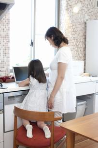 キッチンでノートパソコンを見るお母さんと娘の写真素材 [FYI04192891]