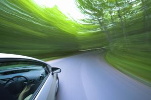 新緑の中を走るハイブリッドカーの写真素材 [FYI04202994]
