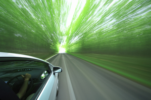 新緑の中を走るハイブリッドカーの写真素材 [FYI04202996]