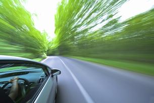 新緑の中を走るハイブリッドカーの写真素材 [FYI04202997]