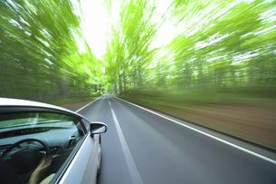 新緑の中を走るハイブリッドカーの写真素材 [FYI04202998]