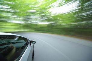 新緑の中を走るハイブリッドカーの写真素材 [FYI04202999]