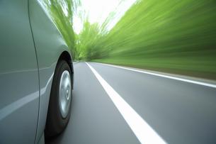 新緑の中を走るハイブリッドカーのタイヤの写真素材 [FYI04203007]