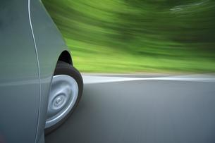 新緑の中を走るハイブリッドカーのタイヤの写真素材 [FYI04203008]